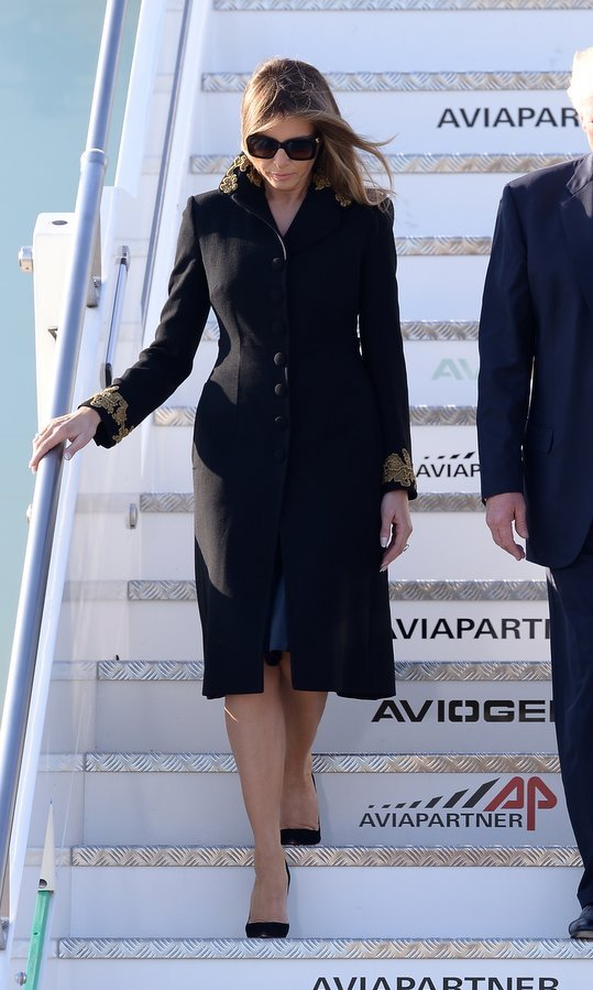 The First Lady stepped off Air Force One in a demure black single-breasted coat with gold sleeve and collar embroidery upon her arrival with her husband at Rome's Fiumicino Airport on May 23, 2017. 