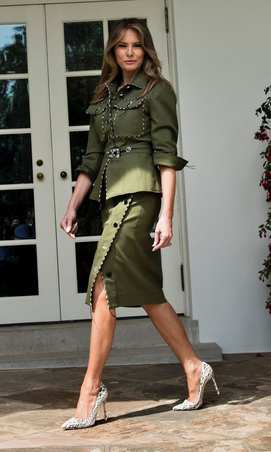 Military style with a twist as Melania walked past the West Wing of the White House in this green skirt suit with black and white trim (and matching heels) on April 27, 2017.