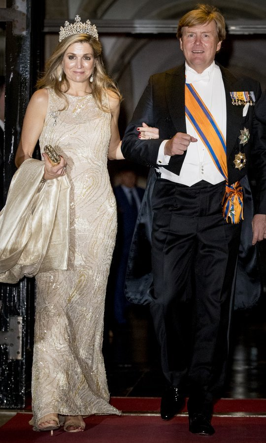 A dapper King Willem-Alexander of the Netherlands escorted wife Queen Maxima, in a gold gown and stunning tiara, to a gala dinner for the Corps Diplomatic at the Royal Palace in Amsterdam.