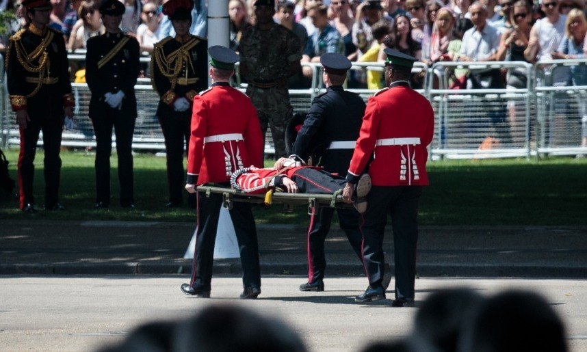 A guardsman was seen being carried off on a stretcher after fainting during the parade. Many participants were affected by the blazing sun.