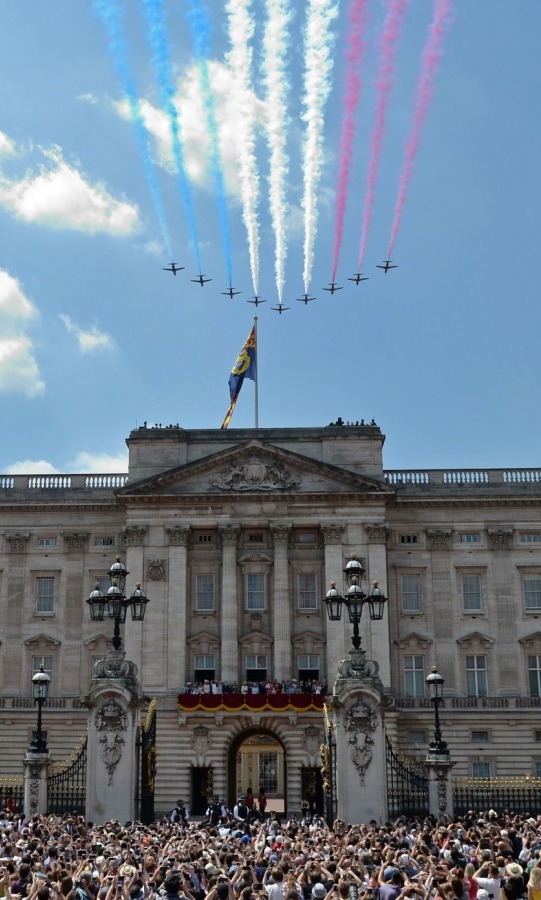 Crowds were elated outside the palace gates as they also enjoyed the patriotic flypast by the RAF with the royal family, who can be seen center, on Buckingham's balcony.