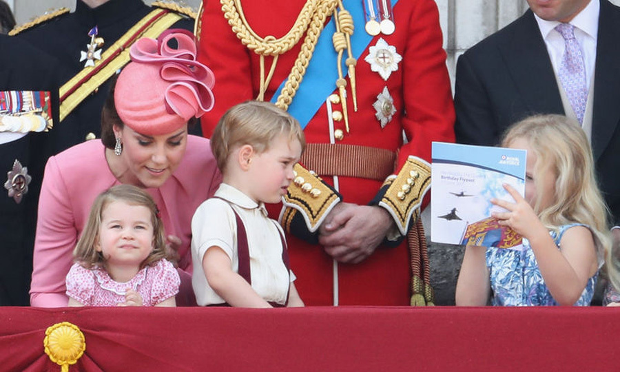 Prince George looked enthralled with what his cousin Savannah Phillips was reading, which seemed to be a pamphlet on the flyover, as they watched.