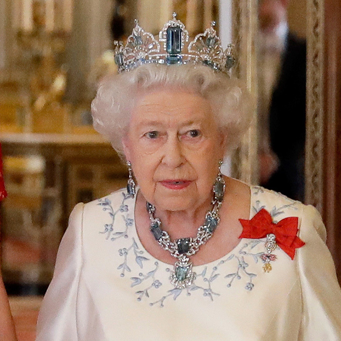 Setting off her blue and white gown, Queen Elizabeth wore the colorful Brazilian aquamarine parure which dates back to the 1950s.