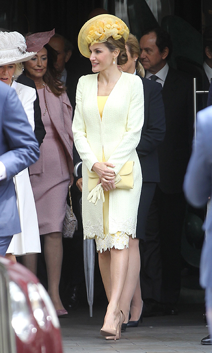 The Spanish royal donned a Felipe Varela tweed coat and lace-trimmed silk dress in sunny yellow for the first events of the day. 