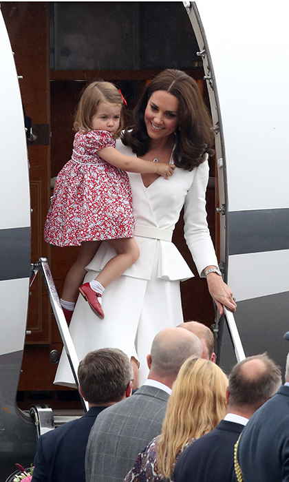 A smiling Kate carried Princess Charlotte in her arms as the family touched down in Warsaw.