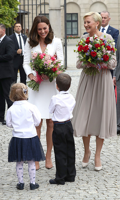 Joined by the Polish first lady, the royal mom-of-two couldn't hold back her laughter as she was charmed by two young wellwishers, who presented her with flowers.  