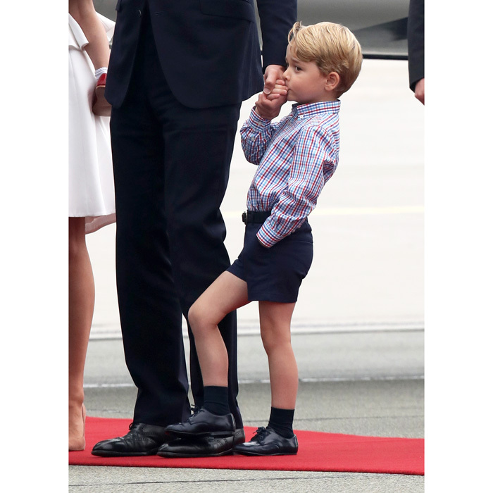 George sweetly kissed his father's hand, following the royal family's arrival to Poland.