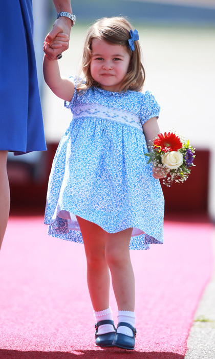 Show-stealing Princess Charlotte looked precious wearing a blue floral smock dress and matching Mary Jane flats. The royal tot completed her look with her trademark hair bow.