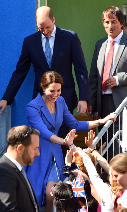 The Duchess gave high fives to fans while visiting a project for street kids in Berlin.