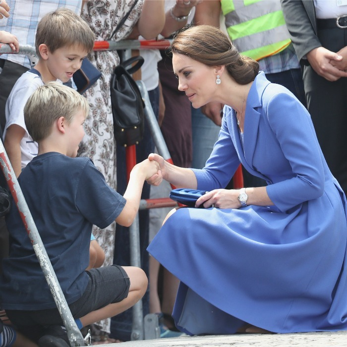 The Duchess shook hands with a young boy during a walkabout in Berlin.