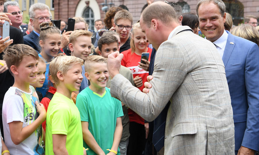 Prince William showed off his muscles while talking to children at the historic market center.