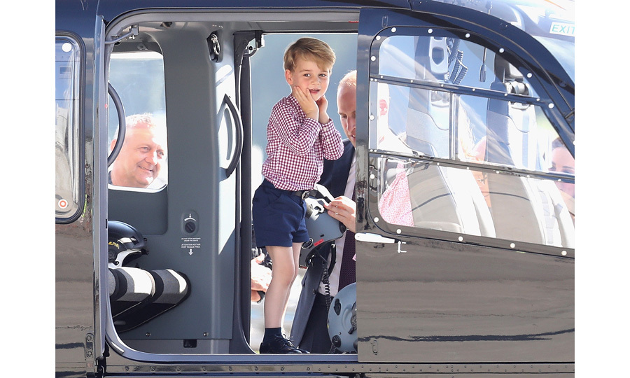 While on the tarmac, the foursome explored an EC145 helicopter, which is the same one the Duke of Cambridge flies with East Anglian Air Ambulance. A beaming George was spotted receiving assistance from his doting father as he tried on a helicopter helmet. The little Prince looked in awe of his surroundings, adorably placing his hands on his face as he stood inside the aircraft.