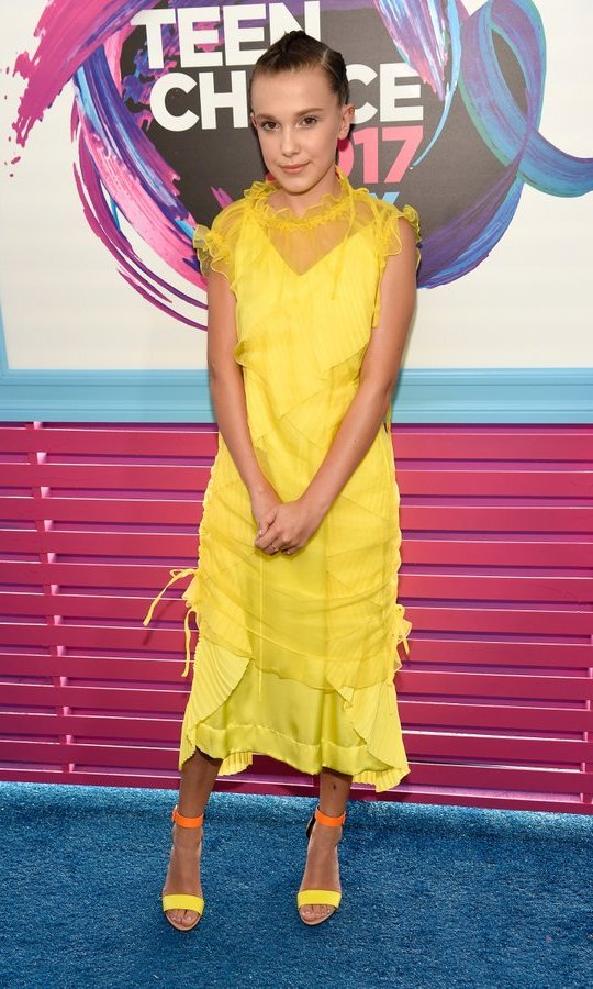 <I>Stranger Things</I> star Millie Bobby Brown continued her style streak at the awards show in this bright yellow dress by Kenzo, worn with Pierre Hardy shoes.