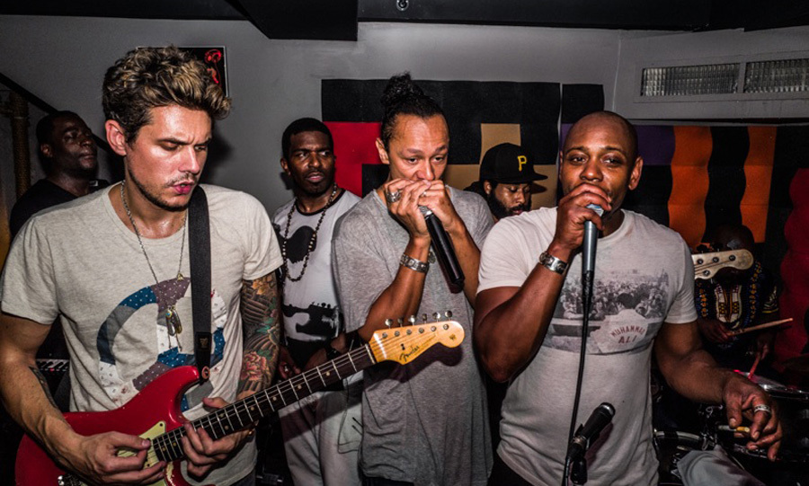 John Mayer surprised partygoers at NYC's Esther & Carol when he hopped on stage to play the guitar alongside Dave Chappelle, who was celebrating 30 years in comedy on August 16.