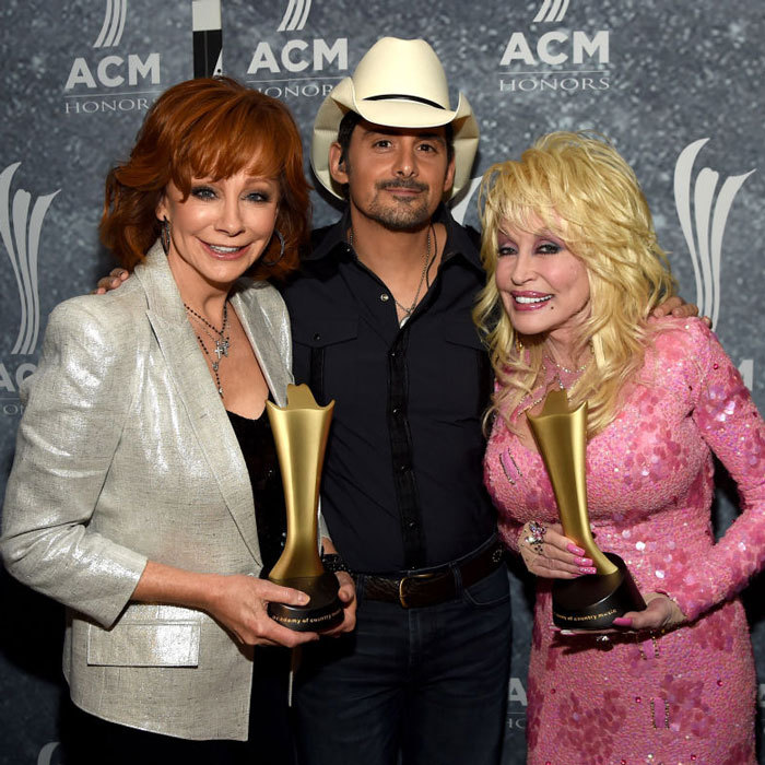 Brad Paisley was one lucky man at the ACM Honors as he was sandwiched between two icons: Reba McEntire and Dolly Parton.