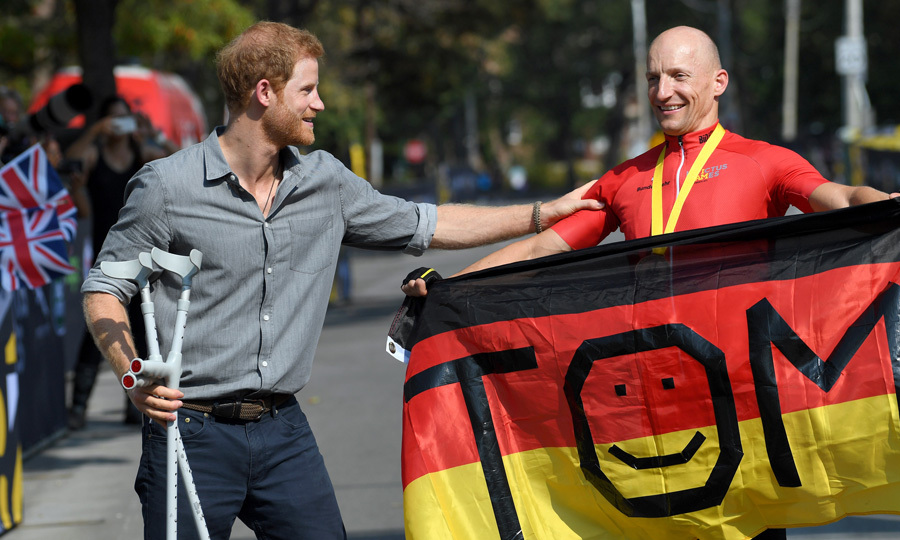 Harry held on to the champion's crutches as he presented him with a medal for cycling.