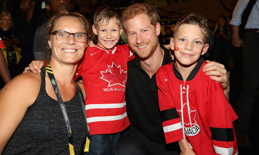 Such a good sport! Harry, who has a way with children, posed with a Canadian family after the wheelchair rugby match.