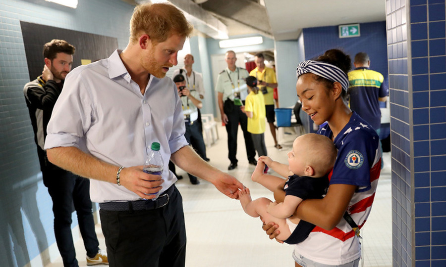 Prince Harry took a moment out of his busy Friday to play with Mike Nicholson's family after he won the gold in swimming.