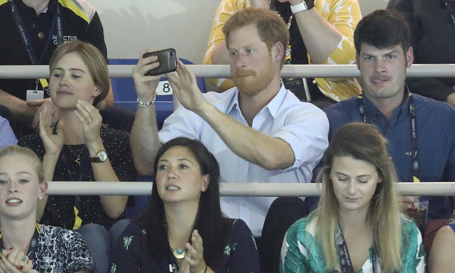 The British royal couldn't help but snap his own photos of the swimming final.