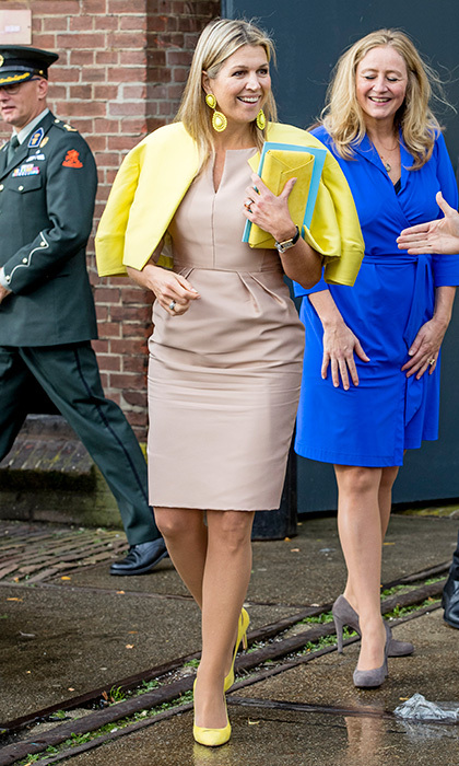 Need a way to add some cheer to your autumn dressing? Add a pop – or four! – of yellow to your outfit. Thanks to those lemony shoes, earrings, jacket and clutch, not even the rain could throw a cloud over Queen Maxima of the Netherlands's sunny look when she attended the Gender & Health of Women Congress In Amersfoort. 