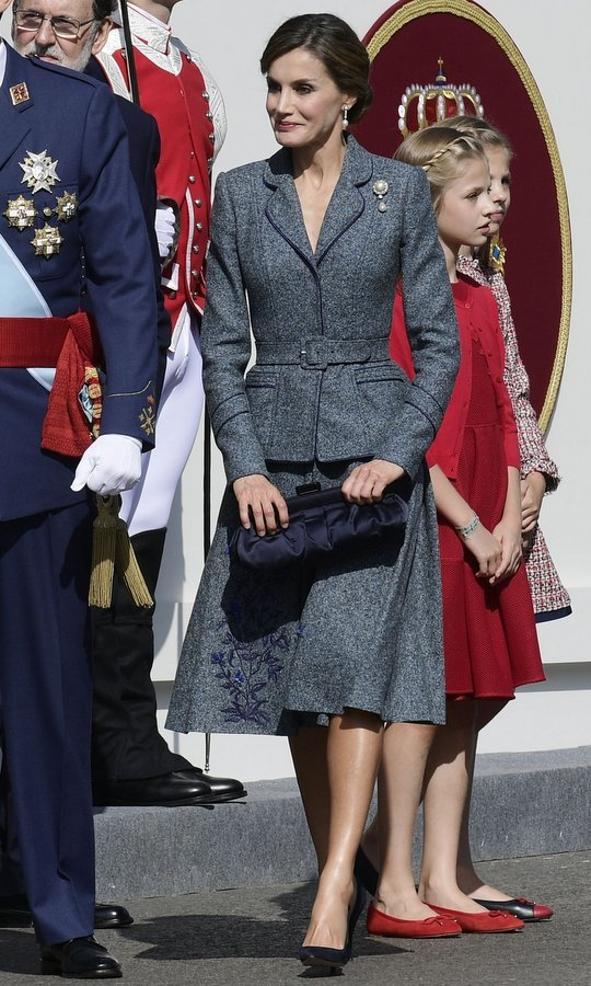 With daughters Princess Leonor and Princess Sofia standing behind her, Spain's Queen Letizia channeled 1950s New Look style in a tailored grey Felipe Varela skirt suit with peplum waist and embroidered hem for the National Day military parade in Madrid on October 12. King Felipe's wife accesorized the outfit with a dark blue satin handbag and pearl and diamond jewelry.