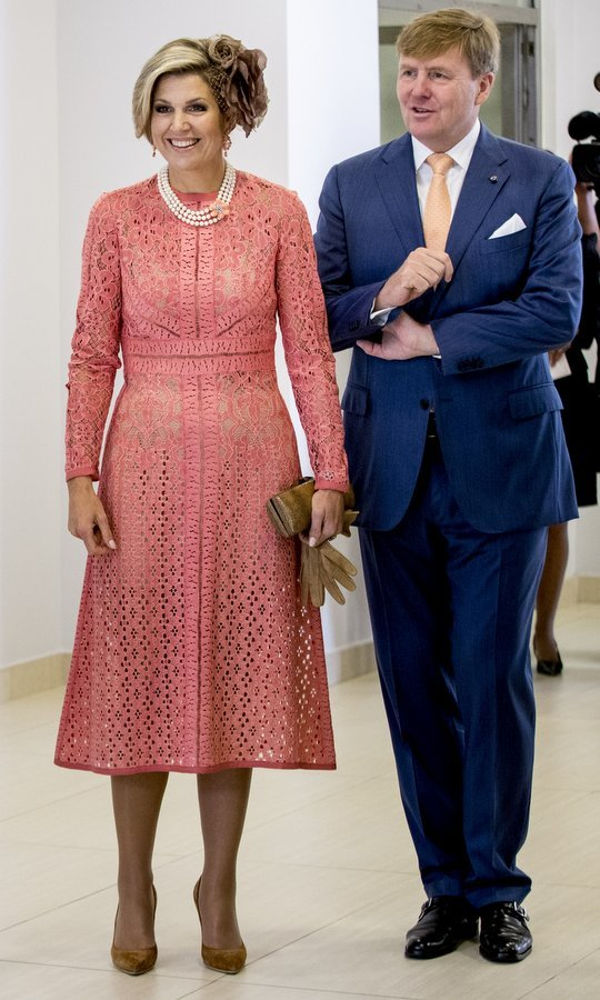 Maxima teamed her coral lace dress with pearls and earth-toned accessories, from her oversized floral fascinator to her suede shoes. The royal was visiting  Lisbon's Champalimaud Centre along with husband King Willem-Alexander, right, during the royal couple's visit to  Portugal. 