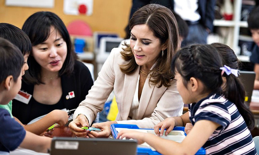 "Crown Princess Mary got hands on during her visit to the Funabashi Primary School during day four of her and Crown Prince Frederik's visit to Japan on October 12. While there, the royals interacted with students and learned the importance of the LEGO ""We Do"" program.