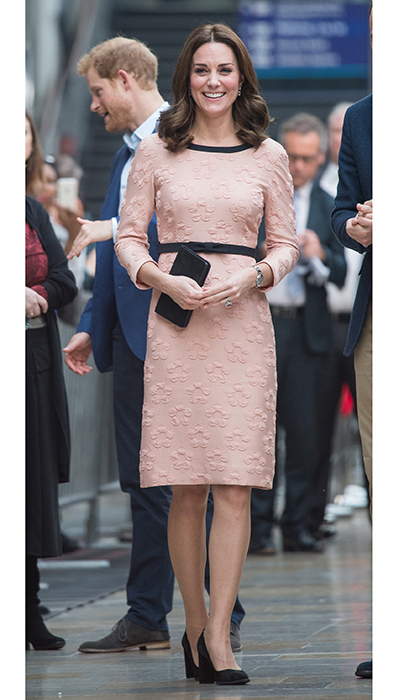 Kate Middleton was pretty in pink in an Orla Kiely dress as she made a surprise appearance at London's Paddington train station with husband Prince William and Prince Harry to meet the cast and crew of the upcoming movie <I>Paddington 2</I>. The Duchess' ladylike look featured a raised floral motif and black details, including a black bow belt which cinched slightly above the pregnant royal's tiny baby bump.