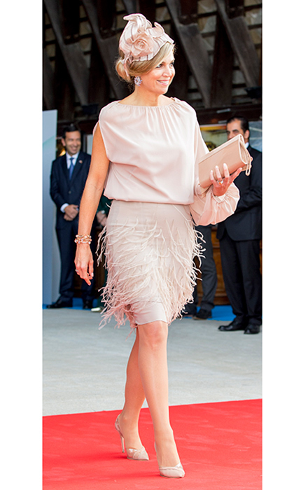 Queen Maxima of the Netherlands wore blush pink on the last day of her tour of Portugal with husband King Willem-Alexander. The fashion-forward royal wore a single-sleeved dress featuring a pretty feather embellished skirt. A matching fascinator, clutch and shoes were the finishing touches on the look.