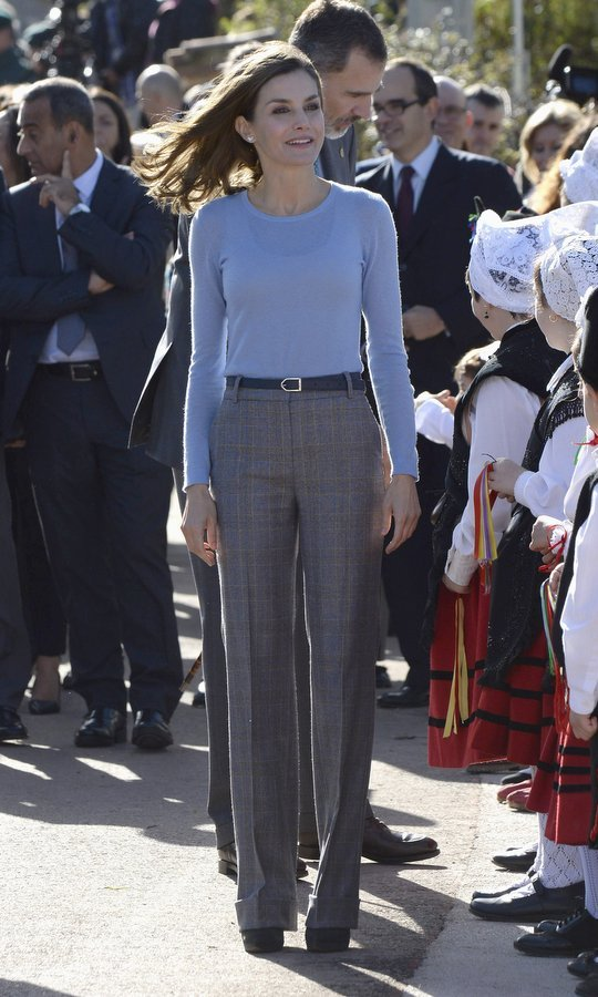 Queen Letizia reached into her closet for some fab fall knits as she visited the village of Poreñu, Spain. We love the simple mix of a blue knit top and menswear-influenced wide leg checked trousers. 
