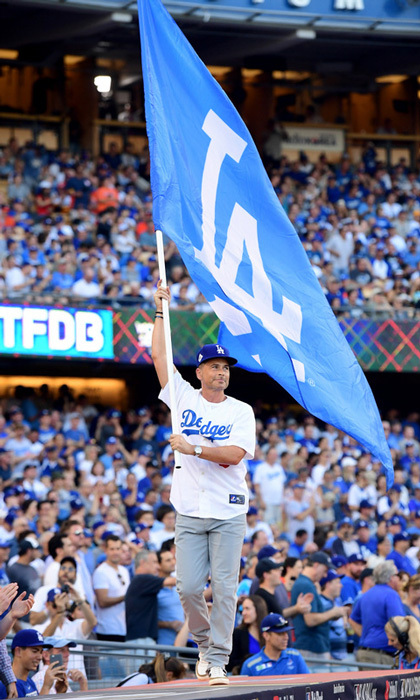 "Rob Lowe showed off his team spirit by waving the Los Angeles Dodgers flag on the dugout. Sporting a white jersey, he also shared an image on Instagram and wrote, ""World Series repping for the boys in blue. @dodgers @mlb #ThisTeam.""