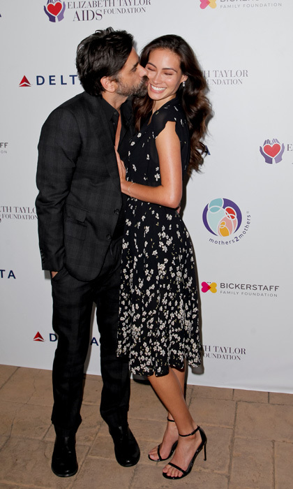 "Have mercy! John Stamos showered his fiancée Caitlin McHugh with kisses on the carpet of the ""mothertomothers and Elizabeth Taylor AIDS Foundation"" benefit dinner in Beverly Hills on October 24. The <i>Fuller House</i> star popped the question to his soon-to-be wife earlier this month during a visit to Disneyland.
