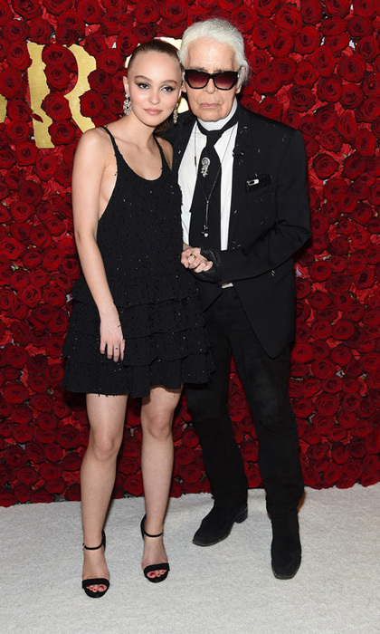 Lily-Rose Depp and Karl Lagerfeld posed in front of a bed or roses during the WWD Honors at the famed Pierre hotel in NYC. The Chanel ambassador escorted the designer down the carpet in a black mini black dress with open-toe heels.