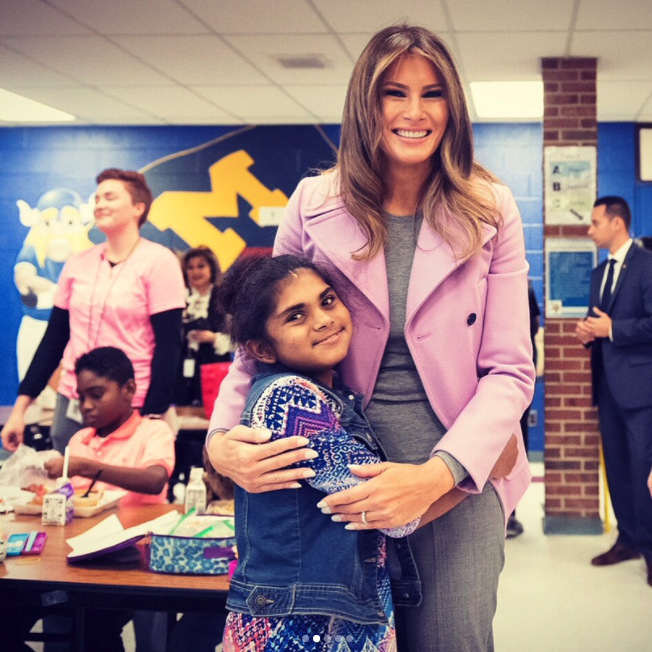 The first lady went to Orchard Lake Middle School in Michigan to meet with students and promote the #nooneeatsalone campaign. For her day with the kids, the former model kept in casual in a Valentino peacoat over a grey sweater and trousers. 