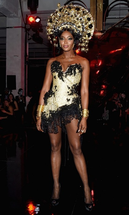 Naomi Campbell turned heads at the amfAR NYC party, wearing an incredible black and gold embellished costume. The 47-year-old fashion queen shimmered in the elaborate gold outfit, which featured a plunging lace mini dress and black high-pumps. Of course, the most eye-catching part was her dramatic and unique looking headpiece.