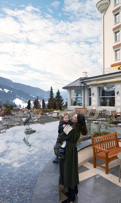 In one of the new images, Tatiana is pictured sweetly carrying her two-year-old daughter outside of the Gstaad Palace in Switzerland, where the shoot took place. The mom-of-two dotingly looked on at her little girl as they stood dressed warmly in coats surrounded by the scenic Swiss Alps.
