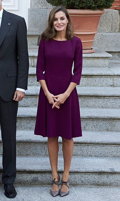 Underneath her stylish trench, Queen Letizia wore a purple day dress by BOSS Hugo Boss with her Magrit shoes. Here she stands on the steps of Zarzuela Palace before the official lunch for the Israeli president and his wife on November 6. 