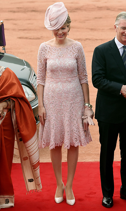 Also traveling abroad is Queen Mathilde of Belgium, who headed to India with husband King Philippe. On November 7, for a ceremonial reception at the Indian Presidential palace in New Delhi, the Belgian Queen wore a dress with powder pink lace overlay, and accessories to match.  