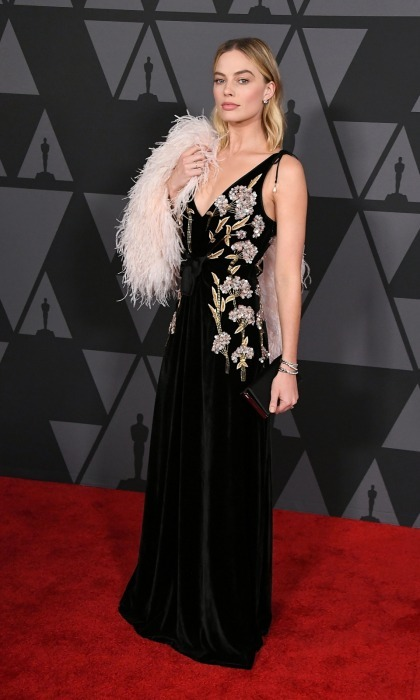 Margot Robbie was ever the exquisite beauty while posing for photos on the carpet. The actress wore a plunging black velvet Altuzarra dress that had floral and beaded embellishments. She added a touch of elegance with a pale pink feathered coat by Prada and jewelry by Sara Weinstock. 