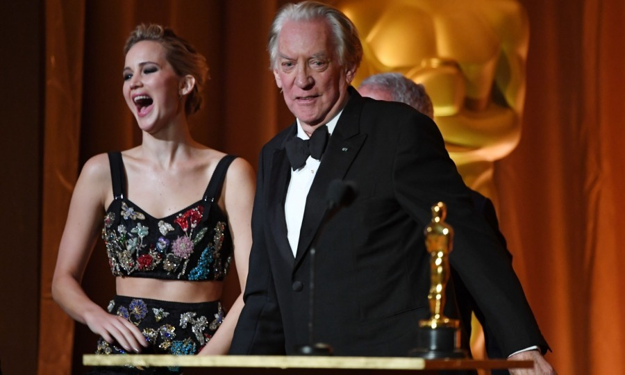 Once inside, Jennifer, who wore an intricate two-piece Alexander McQueen gown, presented an honorary Oscar to her <i>Hunger Games</i> co-star Donald Sutherland. Clearly, she was still giddy from all that photobombing!