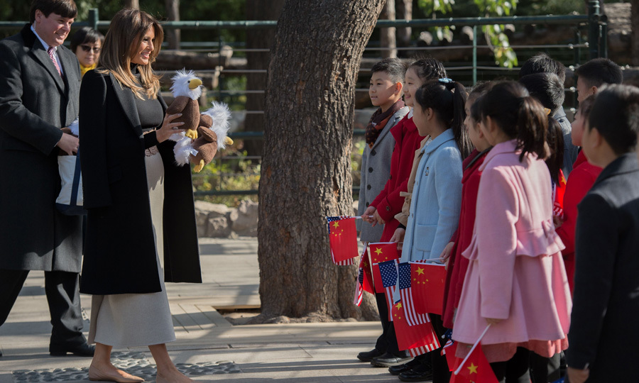 The First Lady gifted children holding American and Chinese flags stuffed bald eagle toys that were made in America during her visit to the Beijing Zoo on November 10.