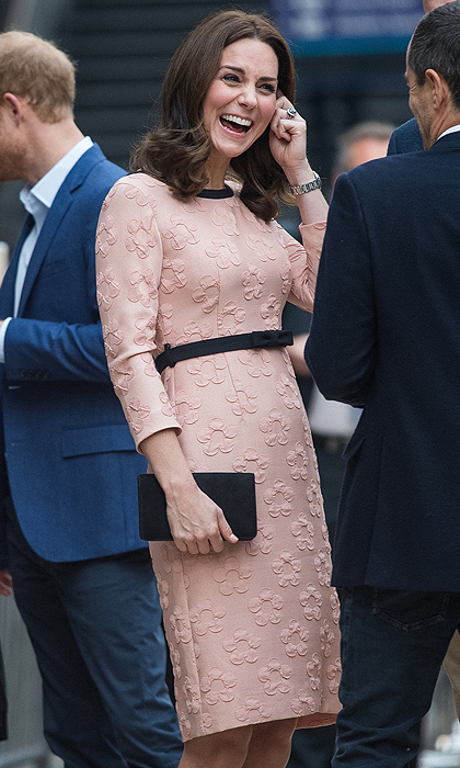 The Duchess of Cambridge looked pretty in pink wearing an Orla Kiely dress that featured a fitted bodice, pencil shape skirt and fabric bow belt for her surprise appearance at the Charities Forum event at London's Paddington train station.