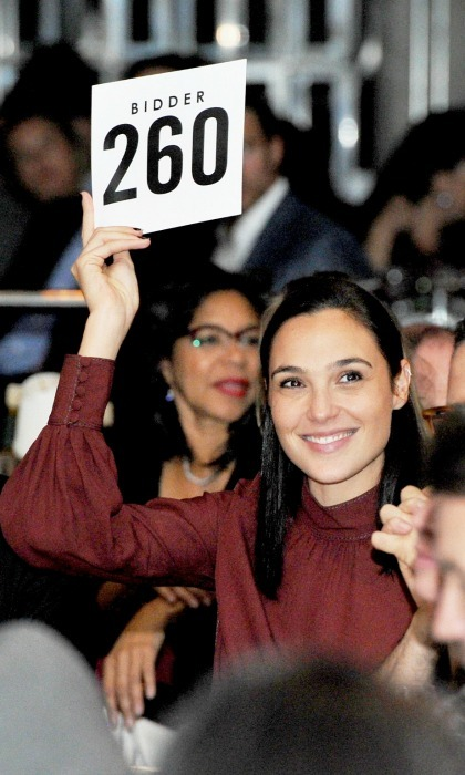 Bidder 260, also known as Gal Gadot, was among the starry crowd at the 2017 GO Campaign Gala in L.A. as well. The <i>Wonder Woman</i> actress put up a bid at the fundraiser, looking elegant in a red wine-colored blouse and big smile. 