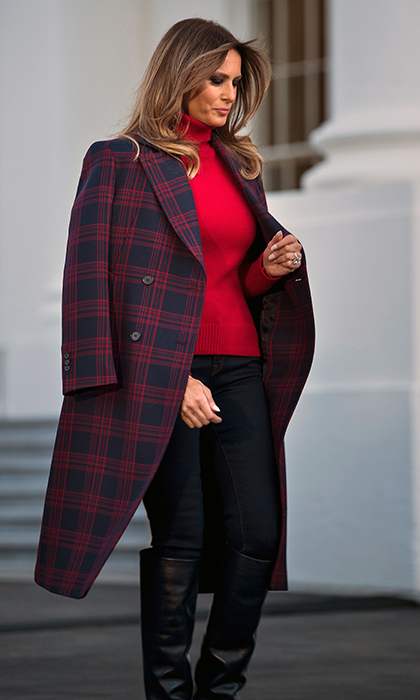 To receive the delivery of the White House Christmas tree alongside son Barron on November 20, First Lady Melania dressed down in a red sweater, dark trousers and knee-high leather boots. Completing the cold-weather ready outfit was a red and navy blue plaid coat by Calvin Klein. 