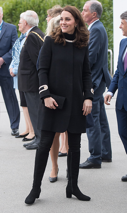 Duchess Kate embraced darker tones the morning of November 22 as she visited Birmingham, England for a day of engagements accompanied by her husband Prince William. The expectant royal once again turned heads, recycling a black occasion coat by British label Goat, with military style details on the sleeves. The classic piece is one we've seen before – she first wore the jacket back in 2014 during a visit to New York.