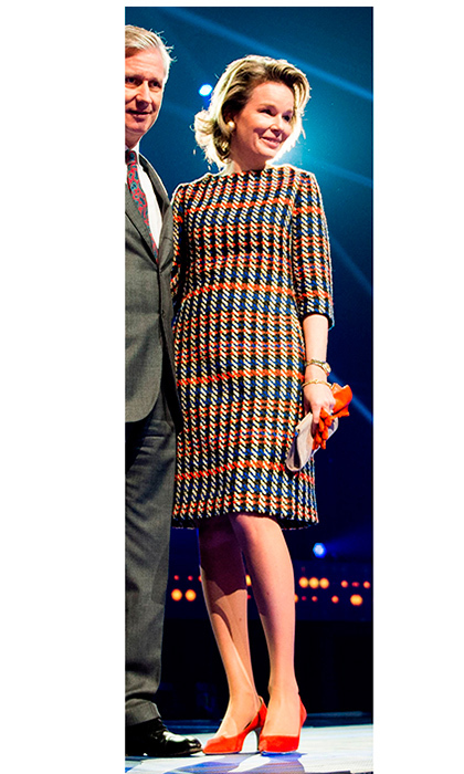 Bright autumnal style? Check! Queen Mathilde wore an orange plaid knit dress with bold and bright heels for a visit to media facilities company Videohouse in Vilvoorde, Belgium on November 29.