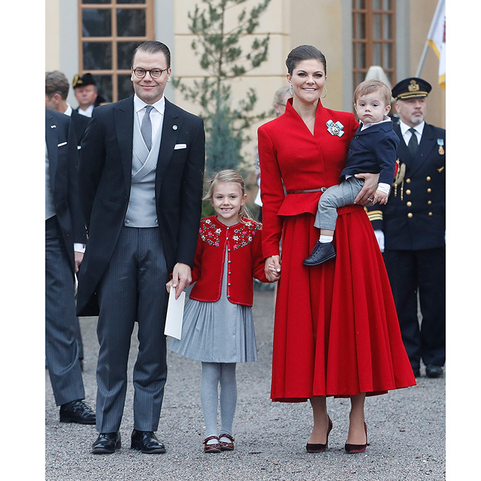 Crown Princess Victoria looked festive along with her husband Prince Daniel, daughter Princess Estelle and son Prince Oscar. The future queen wore a bright red 1950s style peplum jacket and midi-length skirt as she held Oscar, dressed in blue and grey. Estelle was adorable in a red and grey ensemble that matched the palette of her family's attire.