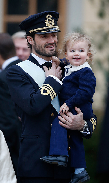 While his dad the prince looked handsome in a military uniform, charming Prince Alexander was adorable in a blue sweater with white knit collar, blue pants and shiny black shoes. 