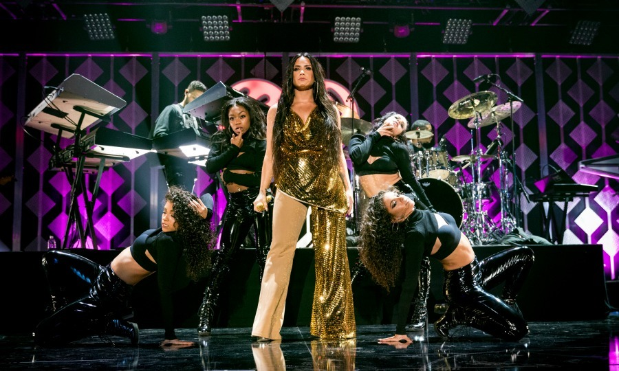 Golden girl! Demi Lovato rocked the crowd while performing at the Jingle Ball 2017 event. The <i>Tell Me You Love Me</i> singer shimmered in a gold Frolov jumpsuit at the holiday concert, which featured one beige pant leg, Giuseppe Zanotti heels and large hoop earrings.