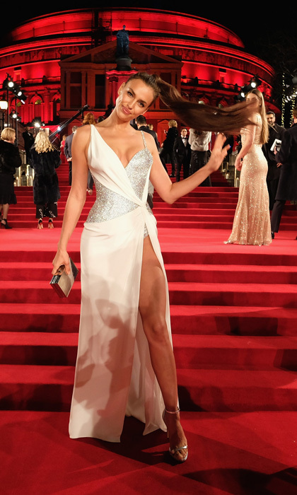 Irina Shayk whipped her hair back and forth as she hit the Fashion Awards red carpet in her Atelier Versace dress. The mom-of-one showed off major leg in the white and silver sparkly number.